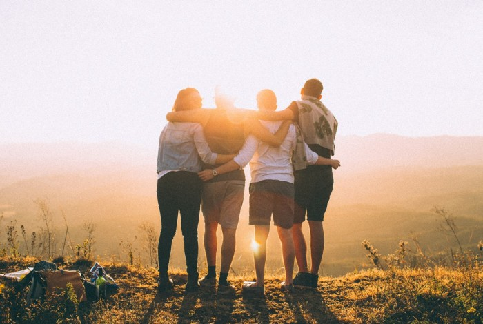 Four friends link arms at sunset