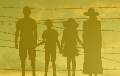 Group of people standing before a barbed wire fence